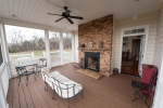 West facing screened-in porch with a beautiful stone fireplace