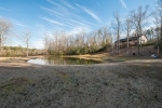 Custom home overlooks the stocked pond and pastures