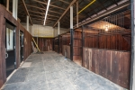 Barn interior consists of 3 12x12 stalls, tack room, workshop area, and hay storage up top