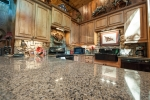 Kitchen outfitted with granite countertops, stone backsplash, ample cabinet space, and under cabinet lighting
