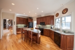 Large kitchen space equipped with hardwood floors, solid surface countertops and custom cherry cabinents
